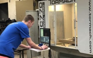 A student works on a CNC router at Phillips High School's fab lab