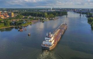 Cargo ship exporting good down a river