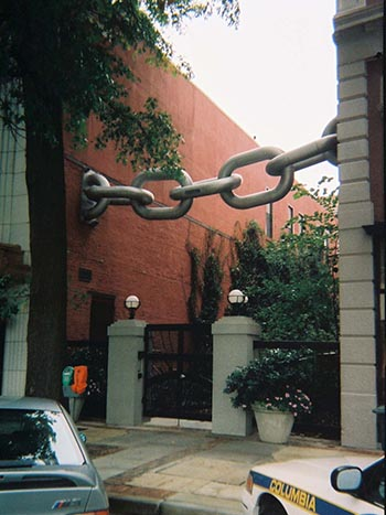 Chain link sculpture connecting an alley between two buildings