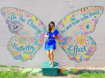"""Woman posing at """"The Butterfly Effect"""" mural in Green Bay, Wis."""