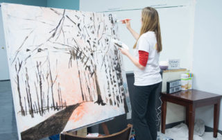 An artist paints during Wausau's Exhibitour event